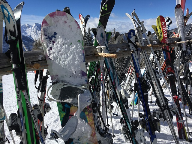 skis and snowboard gear propped up on a rack on the mountain covered in snow