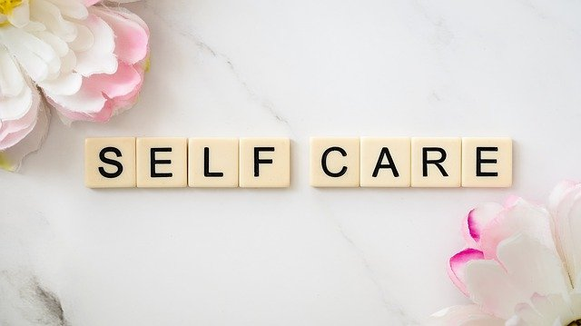 image of scrabble tiles that say self care with pink and white flowers on each side